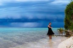 Baile hermoso de la mujer en la playa con una tormenta tropical Foto de archivo