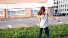 Baile hermoso joven de la muchacha en un parque mujer en los vaqueros que bailan en la calle almacen de video