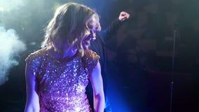 Baile joven de los pares y canto con un micrófono en una barra del Karaoke almacen de metraje de vídeo