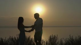 Baile joven feliz de los pares cerca del mar en la puesta del sol Concepto de amor almacen de metraje de vídeo