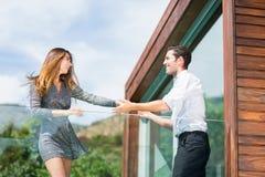 Baile joven feliz de los pares en el balcón en centro turístico foto de archivo libre de regalías