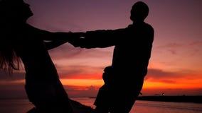 Baile joven romántico de la silueta de los pares que lleva a cabo las manos y que hace girar alrededor en una puesta del sol asom metrajes