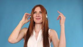 Baile jovial de la mujer joven mientras que escucha la m?sica en auriculares almacen de metraje de vídeo