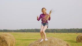 Baile juguetón de la muchacha en pila del heno con la paja en manos en la cosecha del campo Muchacha alegre del adolescente que s almacen de video