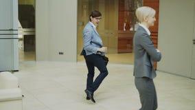 Baile loco del hombre de negocios con la cartera en pasillo moderno mientras que sus colegas que caminaban y que lo miraban sorpr almacen de video