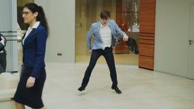 Baile loco del hombre de negocios con la cartera en pasillo moderno mientras que sus colegas que caminaban y que lo miraban sorpr