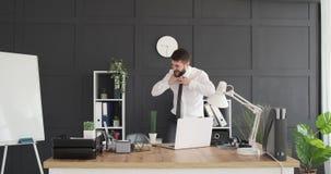 Baile loco del hombre de negocios en la oficina almacen de video