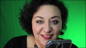 Baile maduro de la mujer de Latina y sonrisa mientras que sostiene el teléfono metrajes