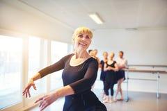 Baile maduro sonriente del ballet de la mujer en un estudio imagen de archivo