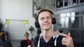 Baile masculino feliz del hombre del inconformista en la oficina con el grupo de hombres de negocios jovenes en el fondo metrajes