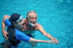 Baile mayor feliz de los pares en piscina junto Padre y ni?o que juegan junto Llevar a cabo las manos y abrazo, abrazo, abrazo, r foto de archivo libre de regalías