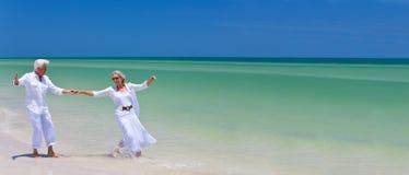 Baile mayor feliz de los pares que lleva a cabo las manos en una playa tropical imagen de archivo libre de regalías