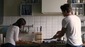 Baile milenario divertido de los pares mientras que cocina junto en la cocina almacen de video