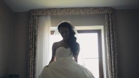 Baile moreno feliz de la novia Mujer atractiva en el vestido de boda que consigue listo para la ceremonia, disfrutando del día