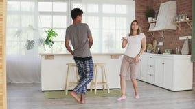 Baile multirracial feliz de los pares en los pijamas que llevan de la cocina que escuchan la música por la mañana en casa Tiro a  almacen de metraje de vídeo