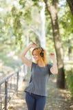 Baile positivo, lindo, sonriente de la muchacha con los auriculares en un fondo del parque Concepto de la música Copie el espacio Imágenes de archivo libres de regalías