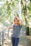 Baile positivo, lindo, sonriente de la muchacha con los auriculares en un fondo del parque Concepto de la música Copie el espacio Imagenes de archivo