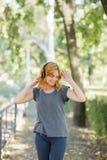 Baile positivo, lindo, sonriente de la muchacha con los auriculares en un fondo del parque Concepto de la música Copie el espacio Fotografía de archivo
