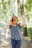 Baile positivo, lindo, sonriente de la muchacha con los auriculares en un fondo del parque Concepto de la música Copie el espacio Foto de archivo libre de regalías