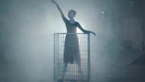 Baile profesional de la bailarina en vestido negro en el estudio en jaula azul grande en el fondo negro con el proyector metrajes