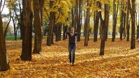 Baile rizado divertido y graciosamente del hombre en el parque del otoño Caída de la hoja en una ciudad en día soleado Naturaleza almacen de video