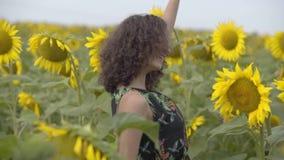 Baile rizado hermoso de la muchacha en el campo del girasol Color amarillo brillante Concepto de la libertad Mujer feliz al aire  almacen de metraje de vídeo