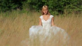 Baile rubio apacible precioso de la novia en un campo de trigo en el vestido nupcial blanco almacen de metraje de vídeo