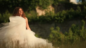 Baile rubio apacible precioso de la novia en un campo de trigo en el vestido nupcial blanco almacen de video