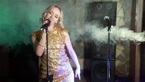 Baile rubio atractivo joven de la mujer y canto con el micrófono almacen de metraje de vídeo