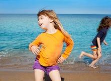 Baile rubio de la muchacha del cabrito en la corrida de la playa y del amigo Foto de archivo libre de regalías