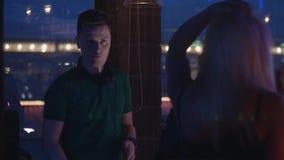 Baile rubio de la muchacha en partido en club nocturno DJ en la placa giratoria agita la mano holidays almacen de video