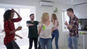 Baile rubio de la muchacha en proyector en el apartamento moderno, gente joven que se divierte en el partido casero metrajes