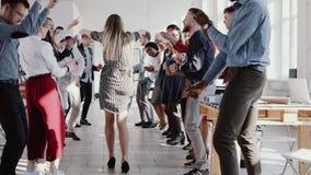 Baile rubio joven hermoso de la mujer de negocios del jefe de la diversión feliz con el equipo multiétnico en la EPOPEYA ROJA de  metrajes
