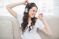 Baile sonriente de la mujer joven mientras que escucha la música Imagenes de archivo