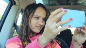 Baile sonriente y tomar de la mujer joven la imagen del selfie con la cámara elegante del teléfono en el coche Imagenes de archivo