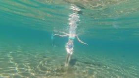 Baile y natación delgados jovenes de la diversión de la muchacha en la costa arenosa almacen de video