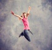 Baile y salto rubios de la muchacha foto de archivo