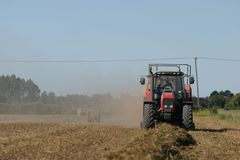 Bailing straw. Tractor working to bale pea straw on the Canterbury Plains, New Zealand royalty free stock photography