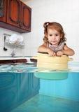 Bain drôle de petite fille dans la casserole dans la cuisine inondée, faisant des mes images libres de droits
