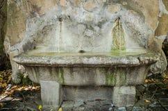 Bain en pierre dans lequel entre une fontaine de l'eau d'une roche à Rome, Italie Photo libre de droits