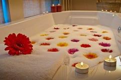 Bain illuminé par des bougies dans la station thermale de santé avec des fleurs photos stock