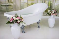 Bain libre de porcelaine dans la salle de bains blanche conçue Bain luxueux blanc, un bouquet des fleurs dans un grand vase La vi Photographie stock libre de droits