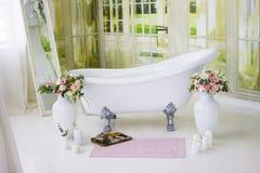 Bain libre de porcelaine dans la salle de bains blanche conçue Bain luxueux blanc, un bouquet des fleurs dans un grand vase La vi Photos stock