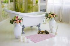 Bain libre de porcelaine dans la salle de bains blanche conçue Bain luxueux blanc, un bouquet des fleurs dans un grand vase La vi Images stock