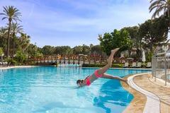 Bains de fille de jeune adolescent et avoir l'amusement dans la piscine ext?rieure images libres de droits