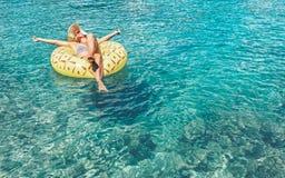 Bains femelles sur l'anneau gonflable de piscine d'ananas dans la lagune clair comme de l'eau de roche de mer photos libres de droits