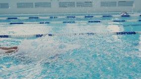 Bains sportifs flexibles forts de jeune femme avec le style de papillon dans la piscine dans le mouvement lent Beaucoup de bulles banque de vidéos