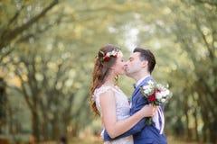 Baiser angélique de jeunes mariés s'étreignant étroitement Photos stock