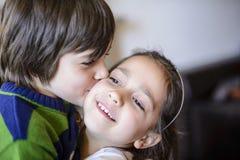 Baiser de frères d'enfants sur la joue Photo stock