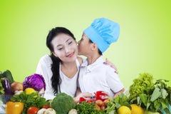 Baiser de garçon sa mère tout en préparant des légumes Photo libre de droits